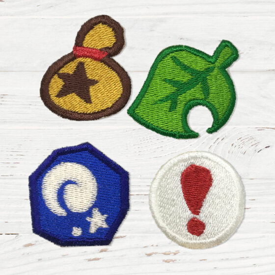 4 Animal Crossing patches. A bell bag, a leaf, a fossil, and a pitfall seed.