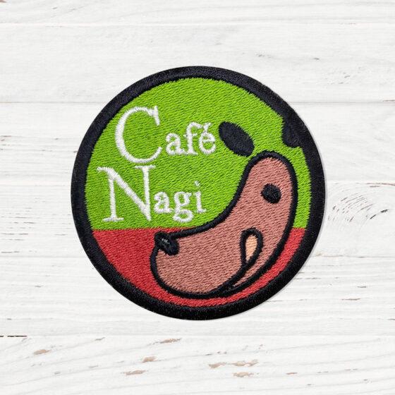 The Cafe Nagi sign. It is half green, half red, with a hotdog shaped like dog.