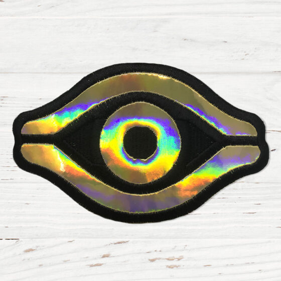 A gold holographic patch in the shape of an eye.