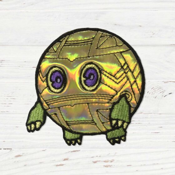 A gold holographic sphere with eyes and green rectangle paws.