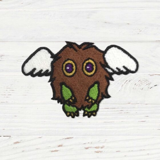 A brown fluffy creature with green hands and white wings.